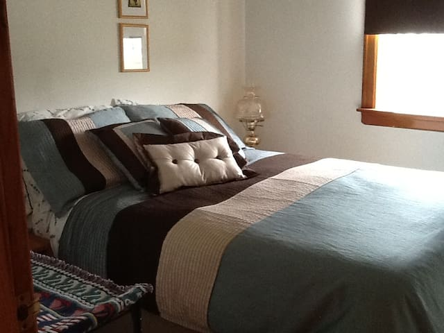 A comfy & clean bed awaiting guests.