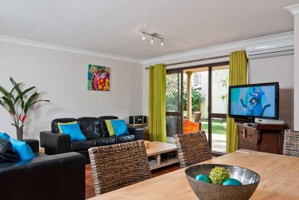 Bright living room with new sofas, flatscreen TV & reverse cycle air con