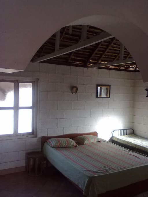 The house has a traditional coconut leaf thatched roof which keeps the room naturally cool .