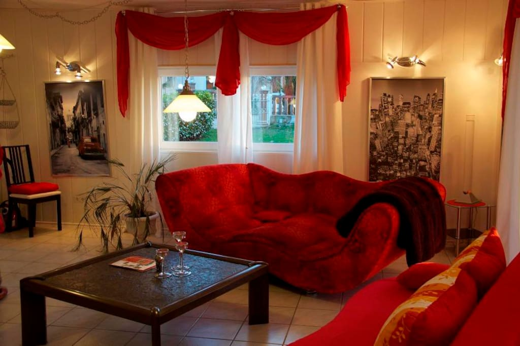 Wohnzimmer: Ein Blick ins Wohnzimmer mit großen Fenstern und Türen. Die Wohnung hat eine eigene Terrasse, Grill sowie einen großen eigenen Garten