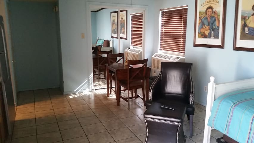 Mirrored closet doors behind table & chairs.