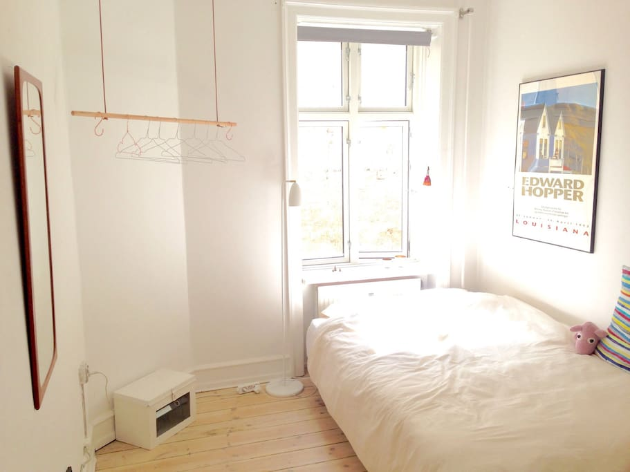 The spacious bedroom in the afternoon light with hangers for your clothes