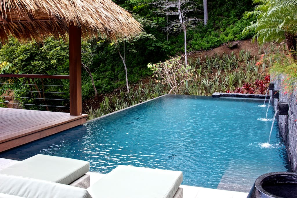 Relax by the infinity pool or cool off in the shade of the Balinese-style thatched roof gazebo