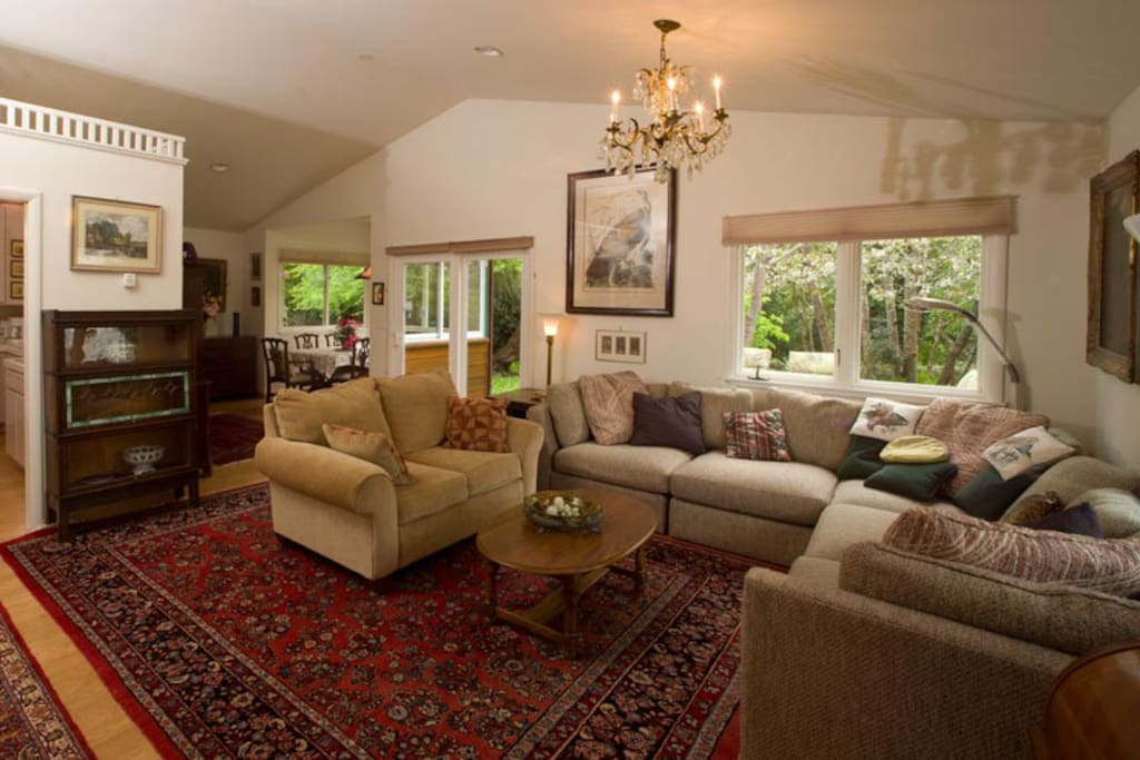 Living room with family heirlooms and carpets is open to the dining nook and the outdoors.