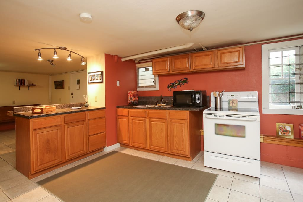 Fully furnished open kitchen with electric stove and microwave.