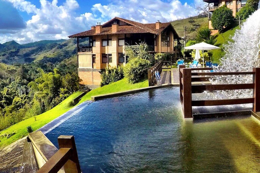O destaque vai para a piscina natural com queda d'água e que possui uma borda infinita direcionada às montanhas de Petrópolis.