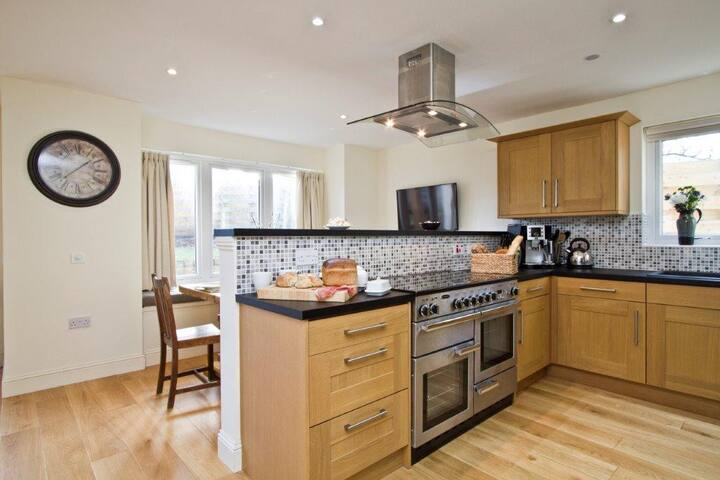 Open plan bespoke designer kitchen with dining area, secondary television area and utility room off the kitchen