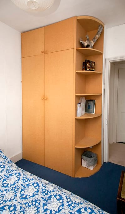 The wardrobe has hanging space and internal shelves and there are bookshelves at the side.