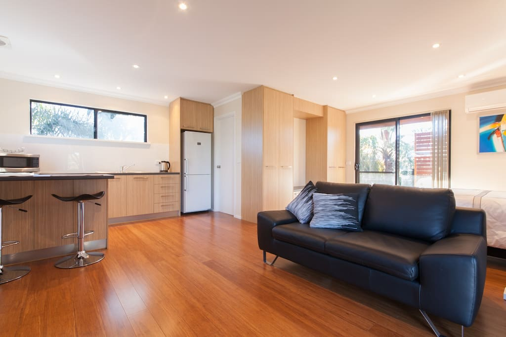 Bright kitchen/living room with leather couch