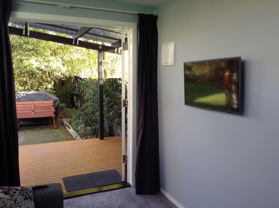 Interior of Sleepout by day looking out to garden showing deck and smart TV