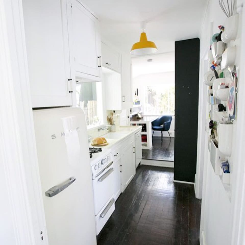 Kitchen area with stove and dishwasher, small office space with desk at the back