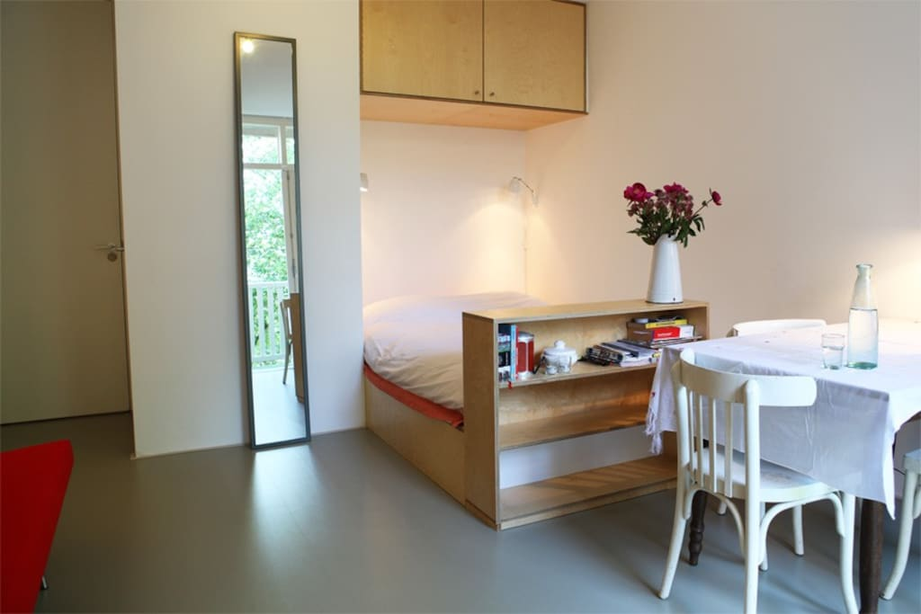 Bellamy Studio: double bed (150 cm), corner of red sofa, own entrance and toilet at the left.