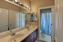 This bathroom is equipped with a shower/tub combo and double vanity.