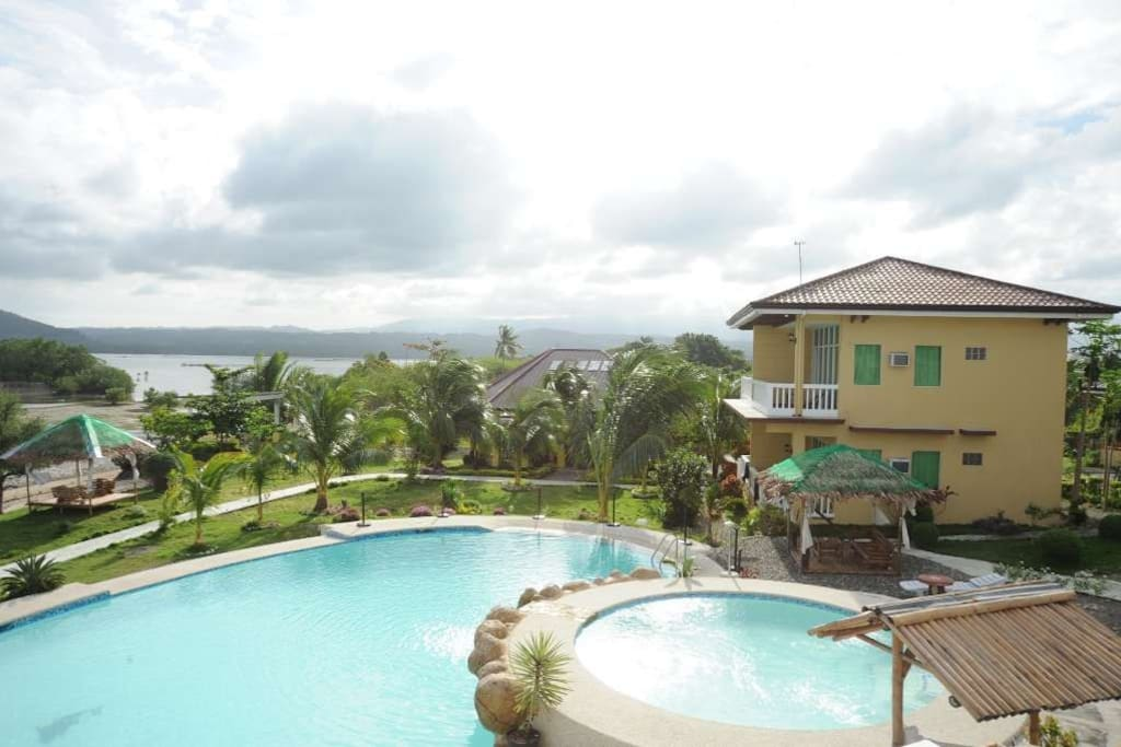 Pool view and 2 story building with deluxe rooms