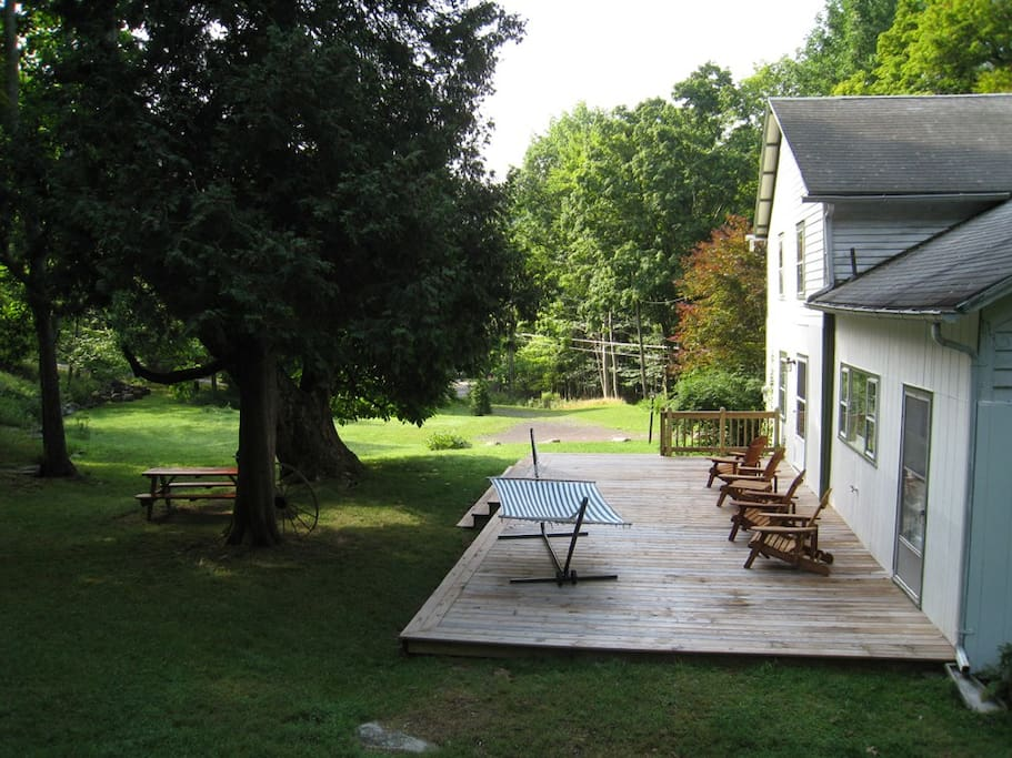 The deck from the huge back yard rock with chairs and hammock.
