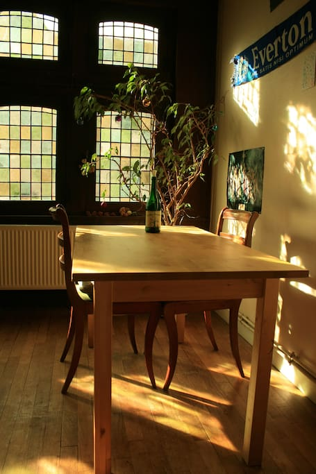 Corner of the living room with dining table. Stained-glass windows facing Cathedral.