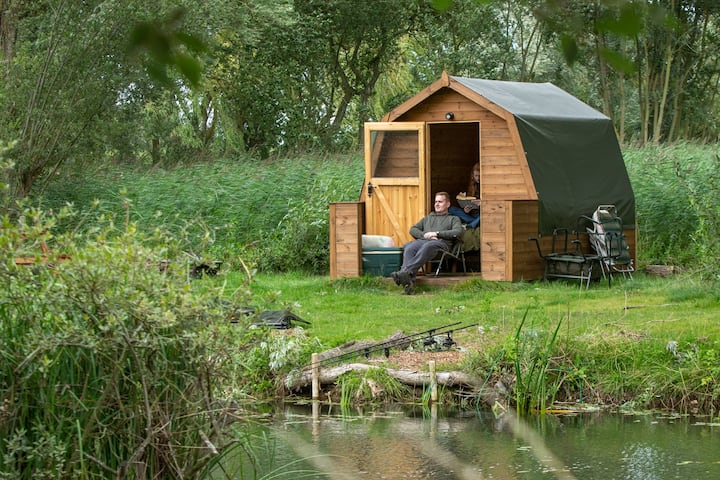 Glamping pod overlooking mature fishing lake