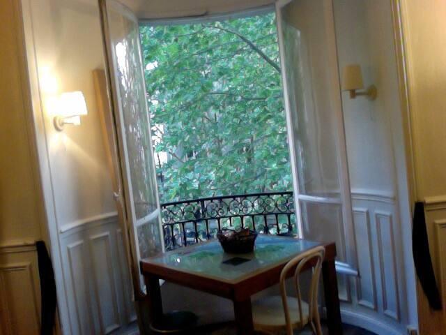 La table de la salle à manger est situé dans un arrondi de l'architecture qui avance au milieu des arbres.