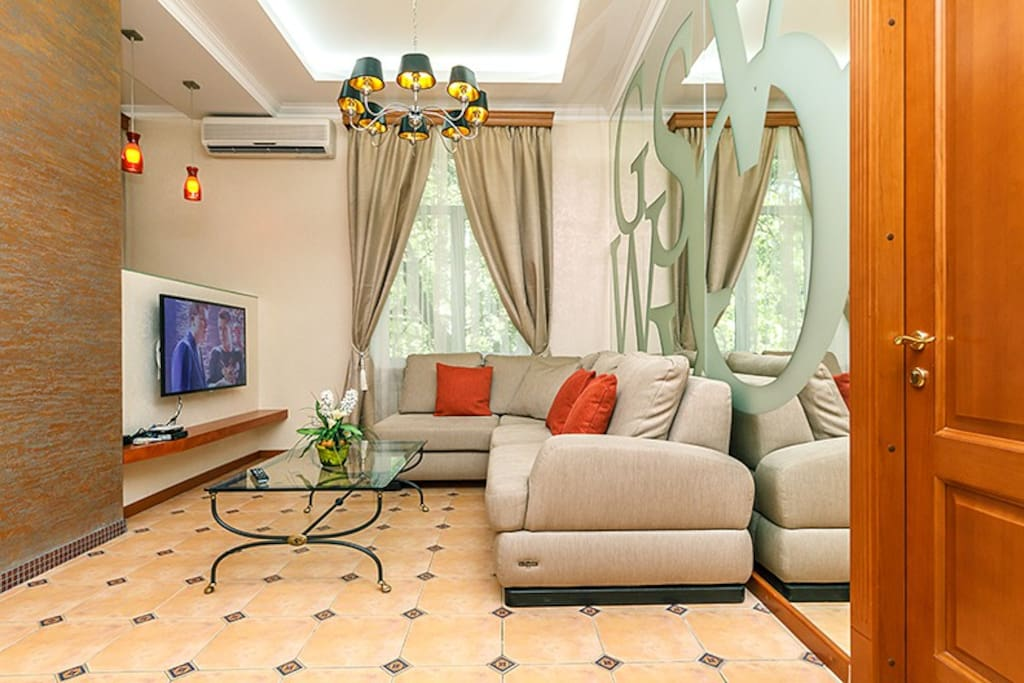 Spacious bright livingroom with big mirror on the wall, free Wi-Fi, flat screen TV, comfortable sofa and coffee table.