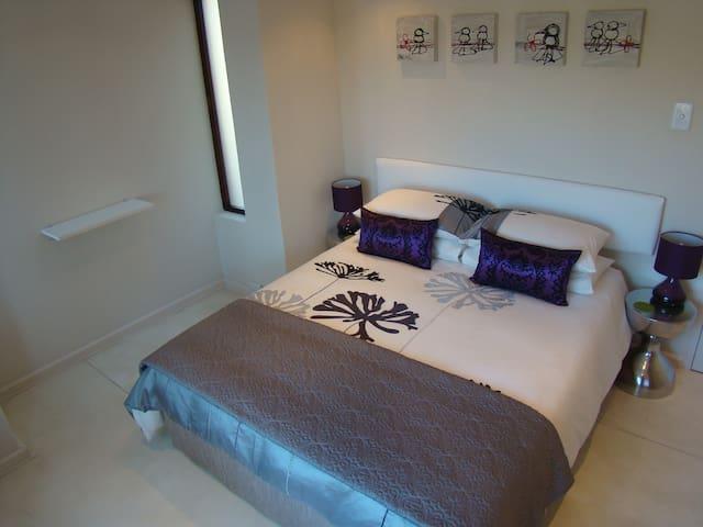 Groundfloor bedroom with queen size bed overlooking the garden and pool area