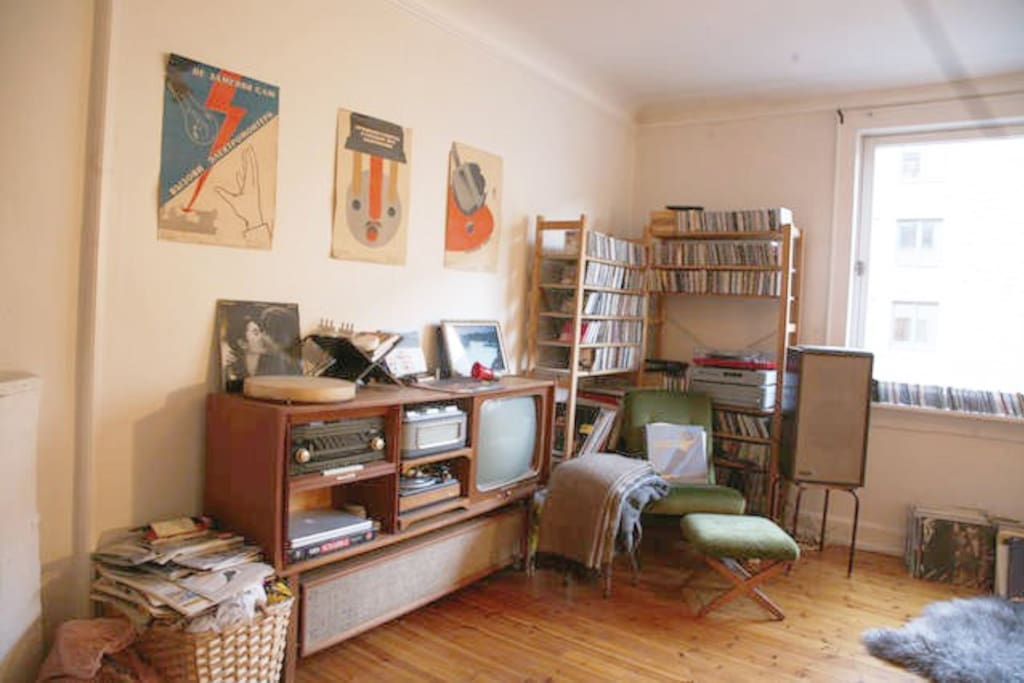 Living room with fireplace, TV, lots of LPs, books and a nice acoustic guitar