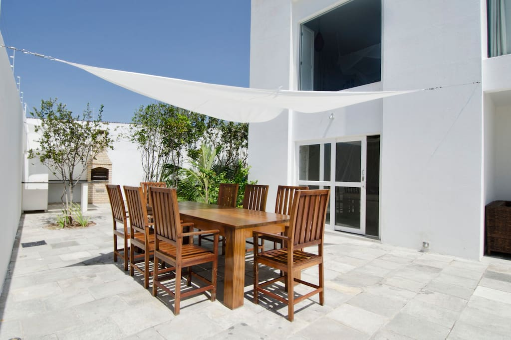 Dining area on terrace with outdoor kitchen incl. BBQ in background.