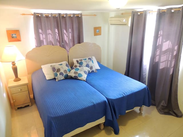 (4th) Bedroom located on the right as you enter the lower level - Made as a King size bed (can be split into (2) single beds) A/C, built in closet, side table & lamp.