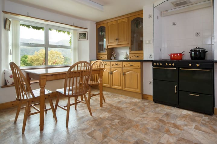 Oak fitted kitchen with range style cooker and dining area, and the same great view.