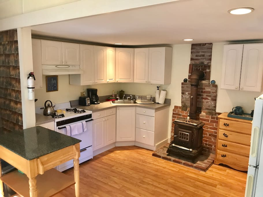 Spacious, modern kitchen with gas range and full fridge and plenty of cabinets.
