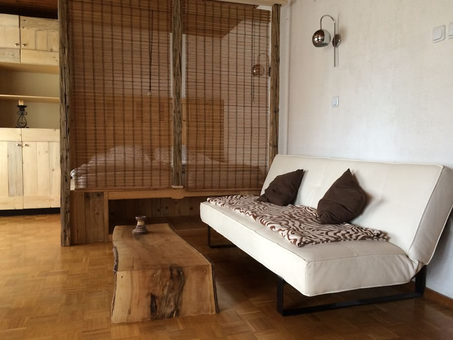 Living room with king size bed behind the wooden curtain