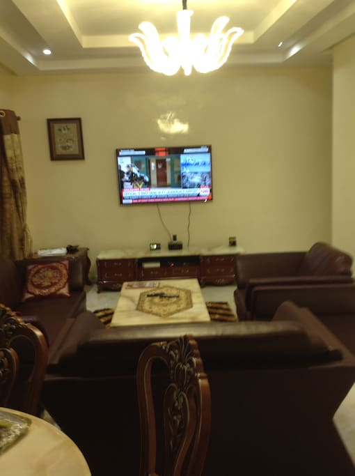 Spacious luxurious living room with real leather furniture, marble flooring, high ceiling and crystal chandeliers