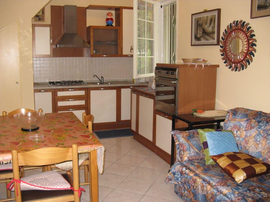 sala con divano letto e cucina a vista piano terra