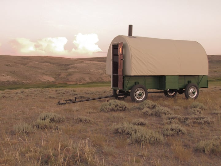 Heward's Fully Restored Sheep Wagon, a green old-fashioned wagon with tan canvas roof and sides with woodstove pipe on a prairie.