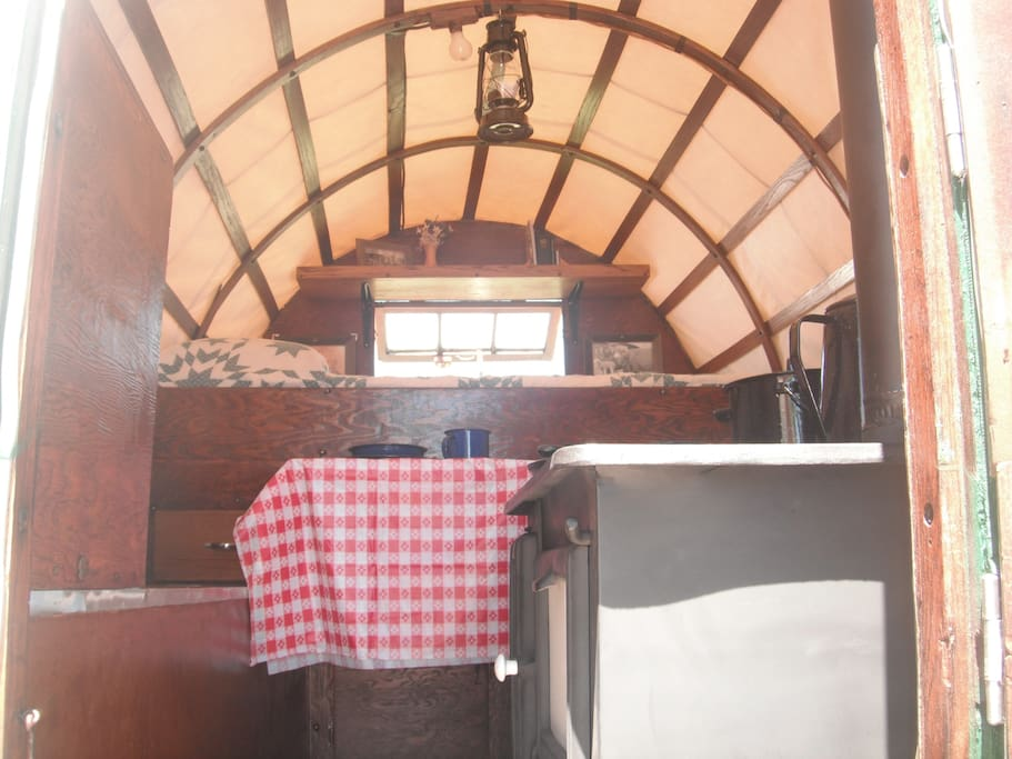 Fully restored wood cook stove/oven, pull out table, full size bed, open and closing back window.