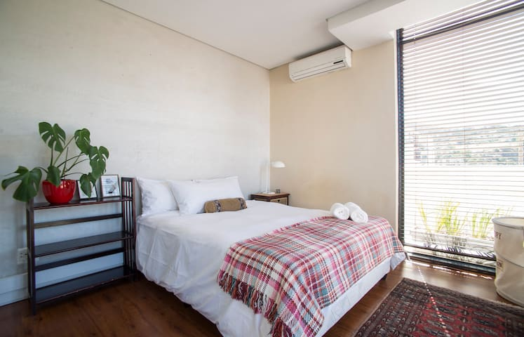 Main bedroom with queen bed, AC and built in cupboards