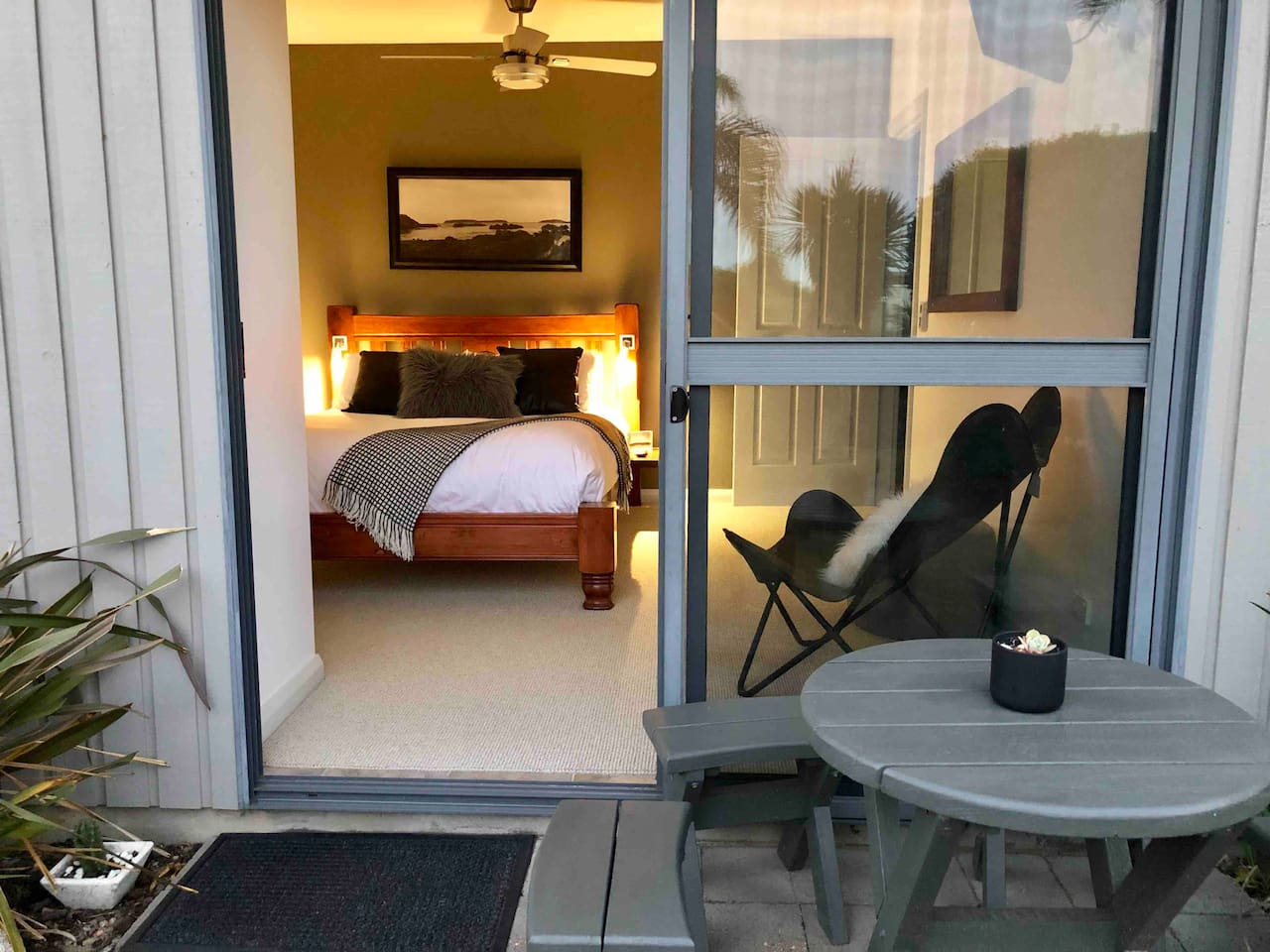 The room has a comfortable queen size bed, fan, heater, tv and chair to sit and relax. The room opens onto a garden with seating options to eat breakfast or sit and read.