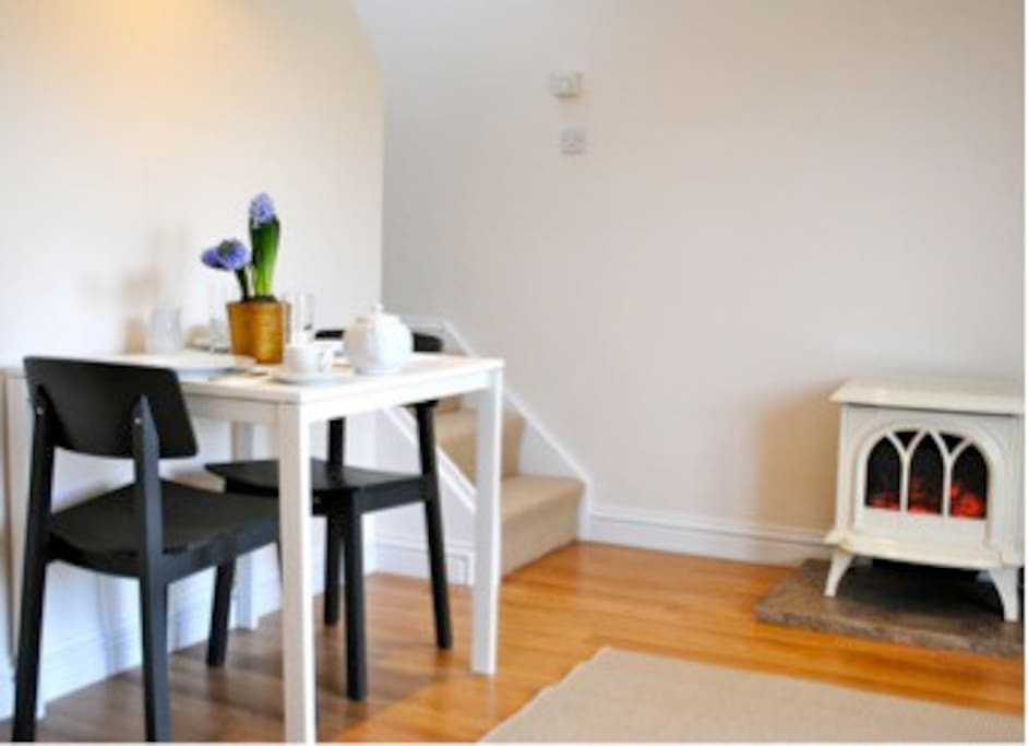 The dining area in the open plan living area, equipped with a log burner for cozy evenings in.