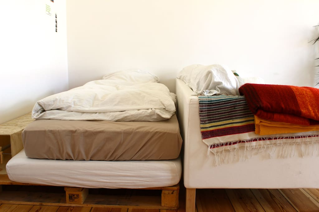the bed of paletts and two mattresses, next to it the couch as a second possibility to sleep on
