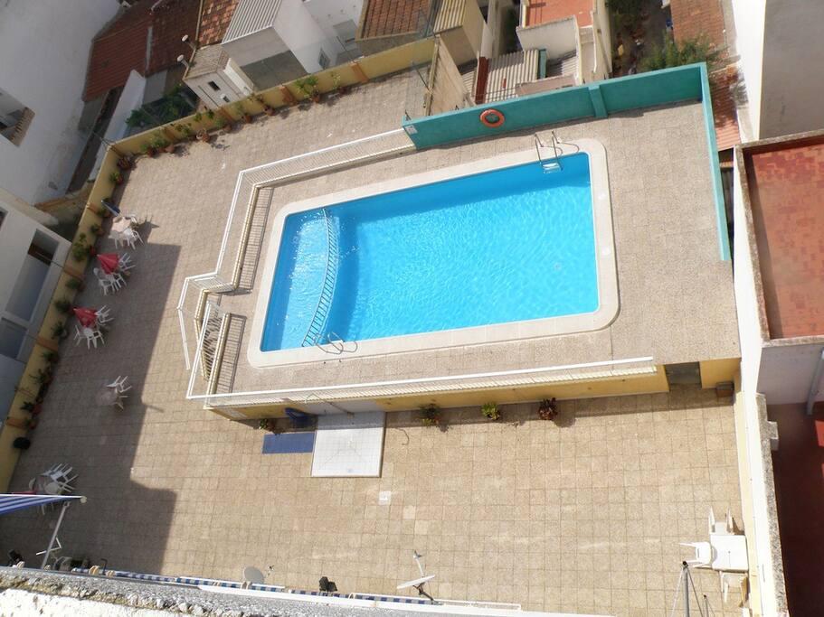 piscina en la primera planta del edificio con solarium muy grande