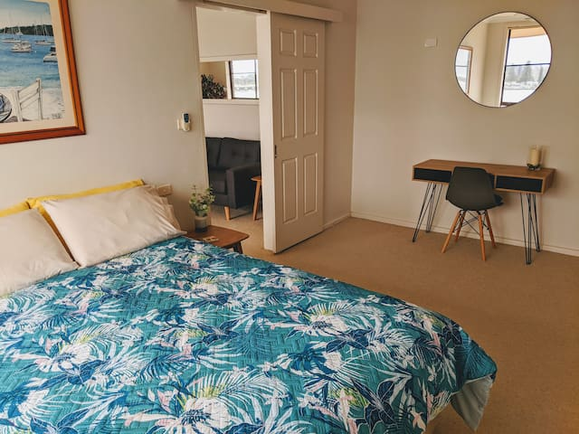 The main bedroom is both spacious and luxurious. With its own en-suite this bedroom is perfect for long sleep ins whilst looking at the view of Tuncurry Harbor. This room now includes a desk for those times when you have to work.
