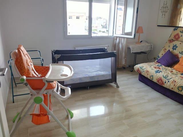 Un lit parapluie et une chaise haute pour bébé dans la chambre d'amis