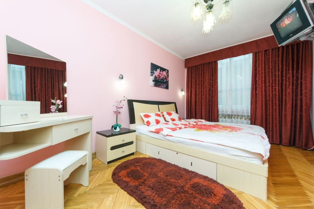 """Separate comfortable bedroom, air conditioning, with """"king"""" size bed, orthopedic mattress, cotton bed linen, towels, large wardrobe, bedside tables, TV on the wall in front of the bed,  dressing table and chair in front of it."""