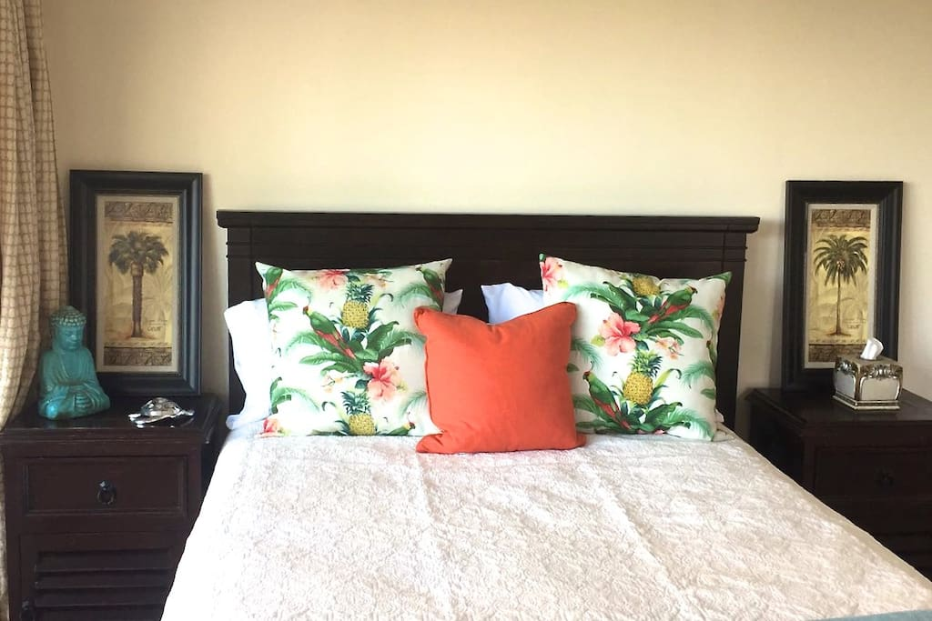 The studio is furnished with solid wood decor, colorful throw pillows, and Hawaiian island accents. There is bedding and other amenities available in the studio.