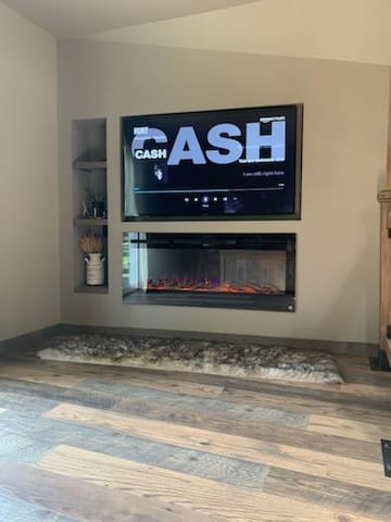 """Cozy rustic living room with a 55"""" TV that includes Amazon Prime streaming, and Netflix!   So you can enjoy watching your favorite shows, while snuggled up by the electric fireplace with 3 adjustable color changing options."""