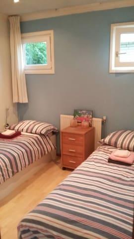 Slaapkamer met 2 bedden en een kledingkast.