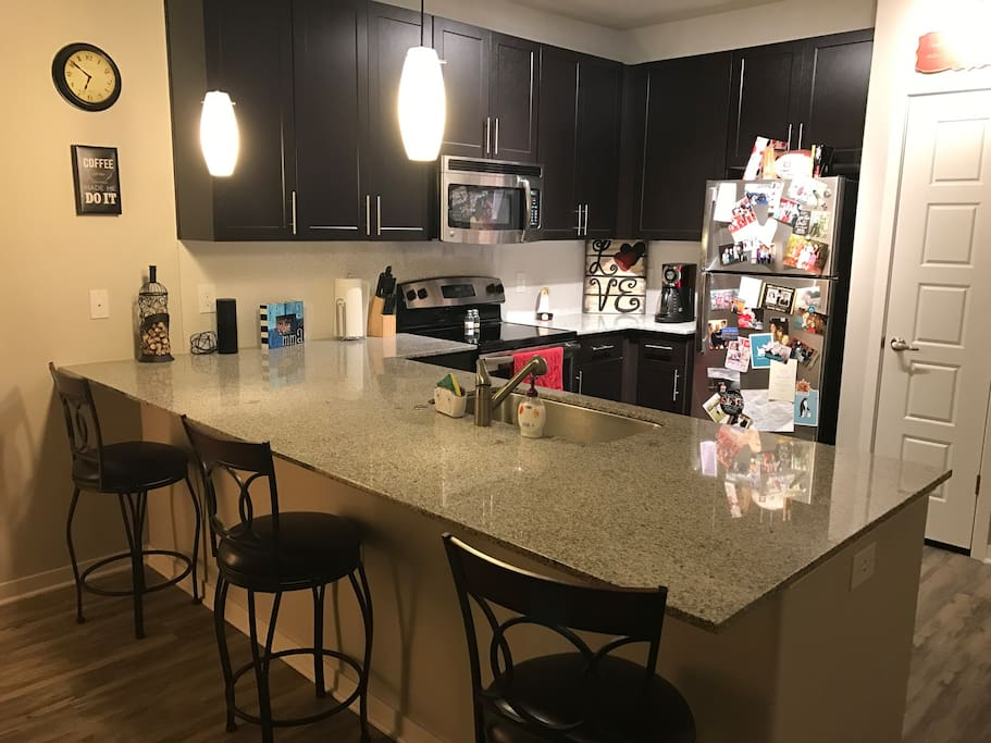Adorable kitchen. Comfy bar stools, granite countertops, stainless steel appliances.