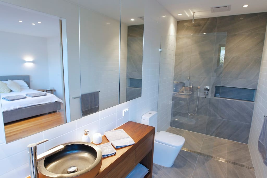5 Star Ensuite Bathroom with big mirrors and luxury overhead rain shower open to Master bedroom with quality linen provided.
