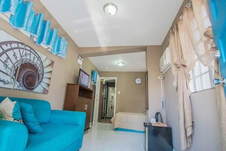 Corner view of your room, including sofa, a comfy double bed and also a small refrigerator if you don't want to walk down to the kitchen!
