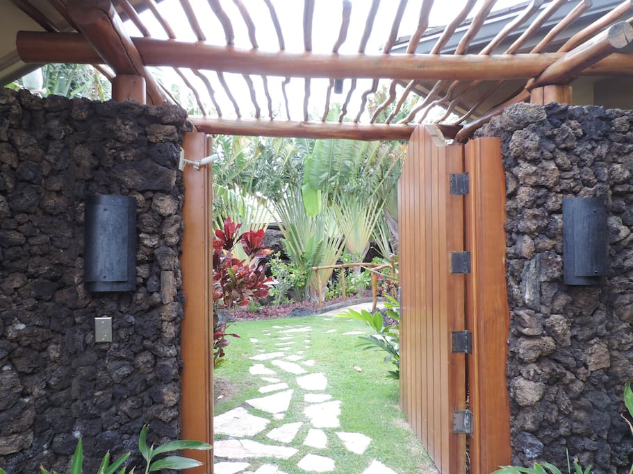 Entry through the gated lava rock wall into the tropical front garden.