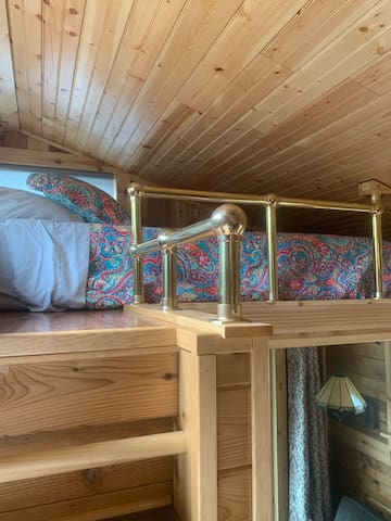 A small loft with a twin mattress. Steps to get up to it.